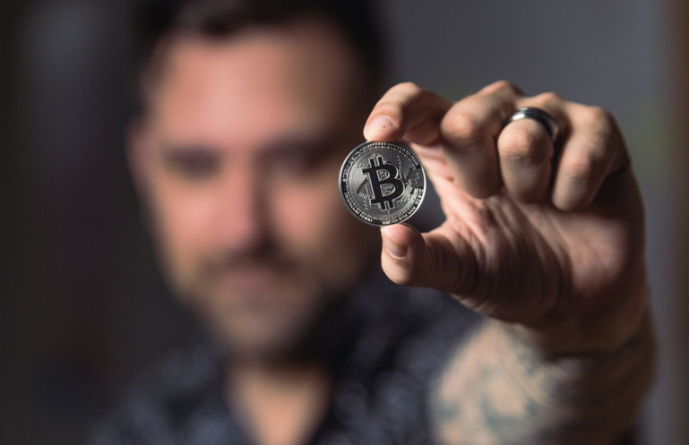Persoană ținând un bitcoin de argint
