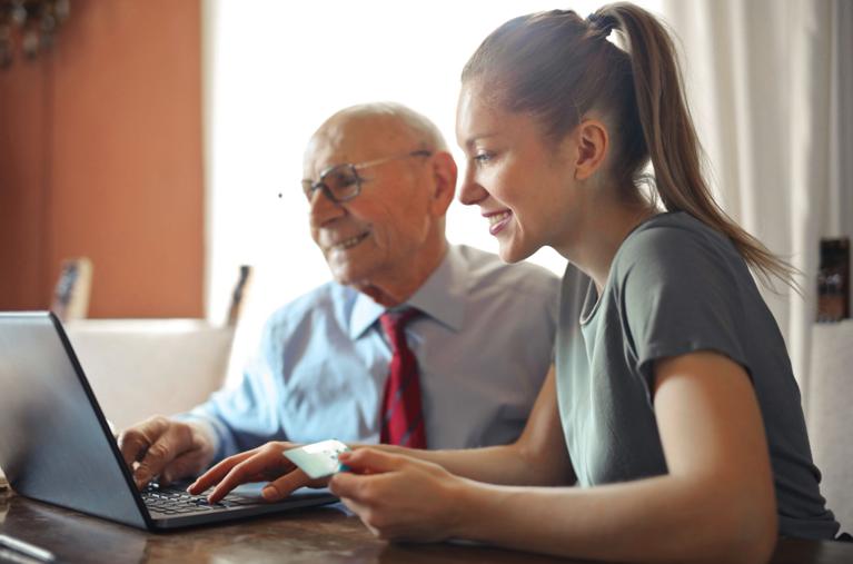 Femeie tânără ajută bătrân cu plata online
